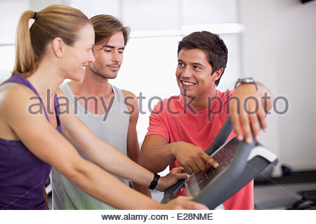 Men helping woman with treadmill in gymnasium - Stock Photo