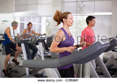 Portrait of smiling woman on treadmill in gymnasium - Stock Photo