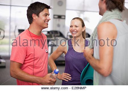 Friends talking in gymnasium - Stock Photo