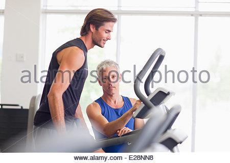 Men talking on treadmill in gymnasium - Stock Photo