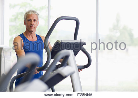 Portrait of smiling man on elliptical machine in gymnasium - Stock Photo