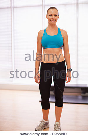 Portrait of smiling woman wearing sports bra in fitness studio - Stock Photo