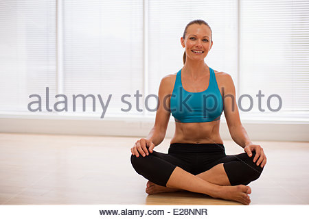 Portrait of smiling woman wearing sports bra in fitness studio - Stock Photo