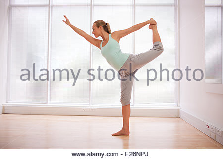 Portrait of smiling woman stretching in fitness studio - Stock Photo