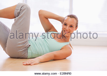 Portrait of smiling woman doing sit-ups - Stock Photo
