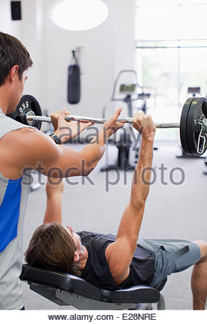 Man spotting friend lifting barbell in gymnasium - Stock Photo