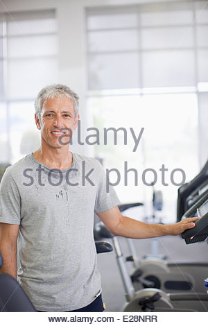 Portrait of smiling man on treadmill in gymnasium - Stock Photo