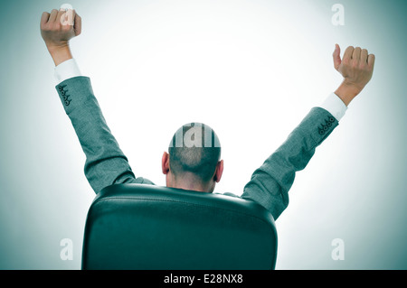 a businessman stretching in the chair of his office - Stock Photo