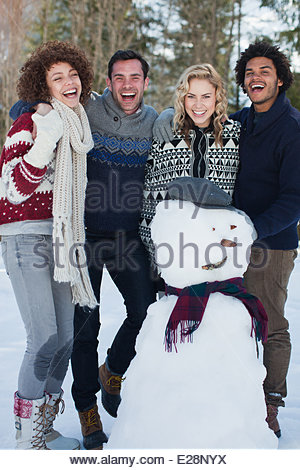 Four friends with snowman - Stock Photo