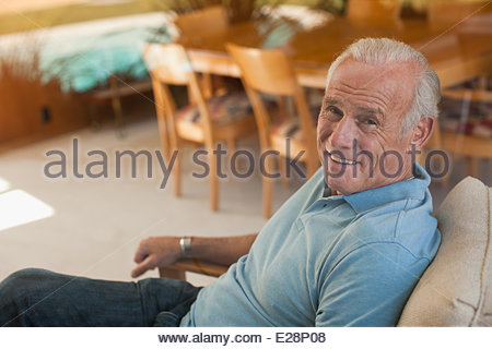 Smiling older man relaxing in armchair - Stock Photo