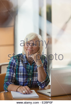 Older woman using laptop indoors - Stock Photo