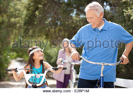 Older couple and granddaughter riding bicycles outdoors - Stock Photo