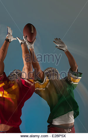 Blurred view of football players reaching for ball - Stock Photo