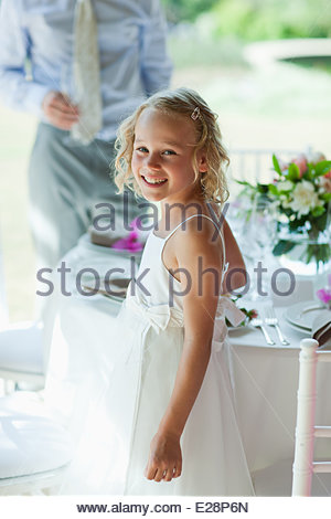 Smiling girl standing at wedding reception - Stock Photo