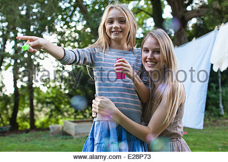 Portrait of smiling sisters blowing bubbles in backyard - Stock Photo