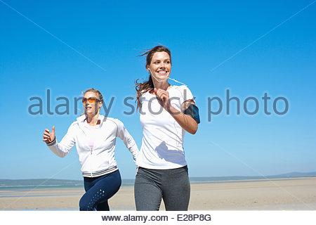 Friends running on beach - Stock Photo