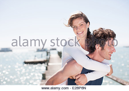 Husband giving wife piggy back ride - Stock Photo