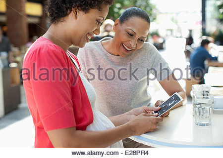 Friends looking at pregnancy sonogram image - Stock Photo