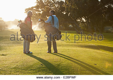 Men carrying golf bags on golf course - Stock Photo