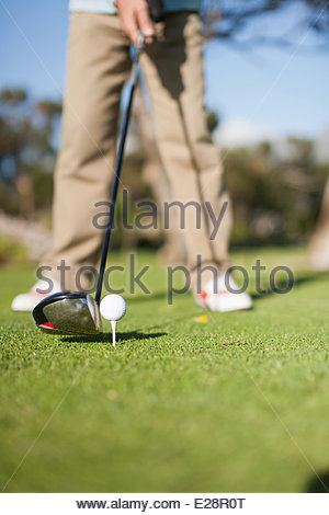 Close up of golf club about to hit golf ball - Stock Photo