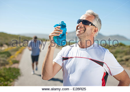 Man drinking from water bottle on remote road - Stock Photo