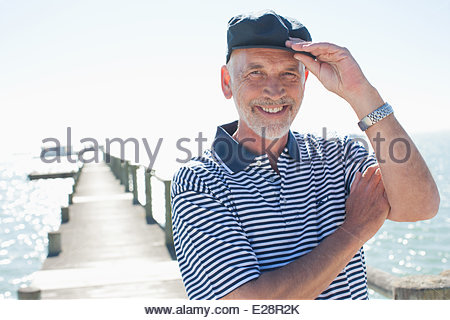 Man in cap standing on pier - Stock Photo
