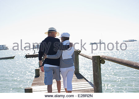 Mature couple walking on pier - Stock Photo