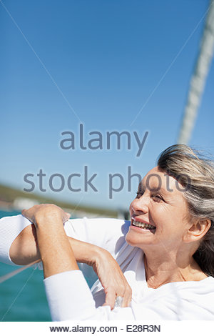 Woman smiling on deck of boat - Stock Photo