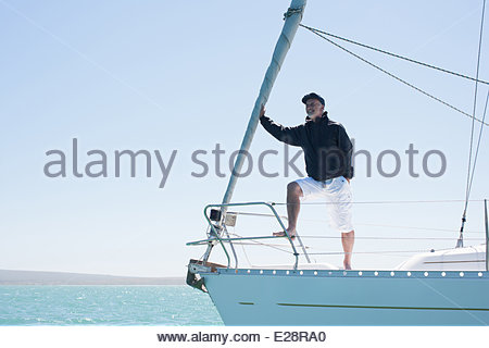 Man standing on deck of sailboat - Stock Photo