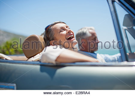 Mature couple driving in convertible - Stock Photo