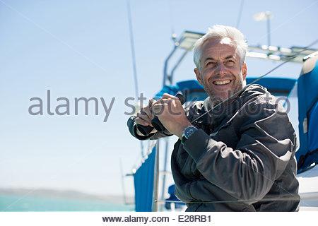 Mature man on sailboat - Stock Photo