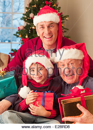 Multi-generation family wearing santa hats and holding Christmas gifts - Stock Photo
