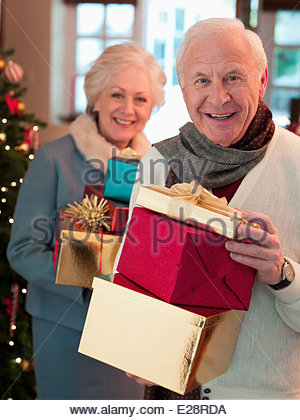 Couple holding Christmas gifts - Stock Photo
