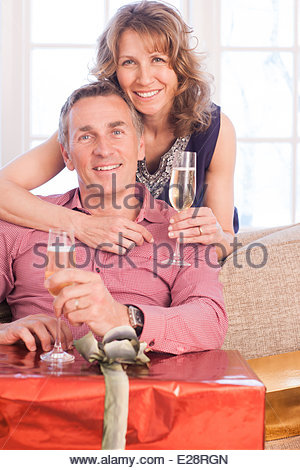 Couple drinking champagne near Christmas gifts - Stock Photo