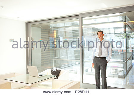 Businessman leaning against glass wall in office - Stock Photo
