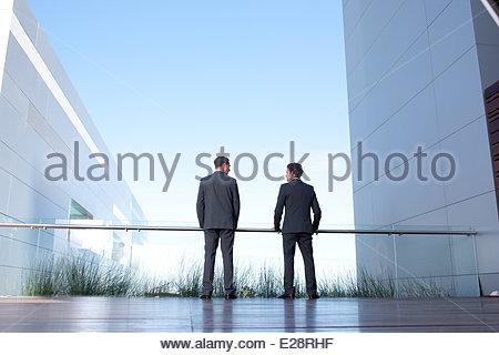 Businessmen standing on balcony - Stock Photo