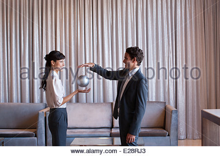 Business people holding silver sphere in hotel lobby - Stock Photo