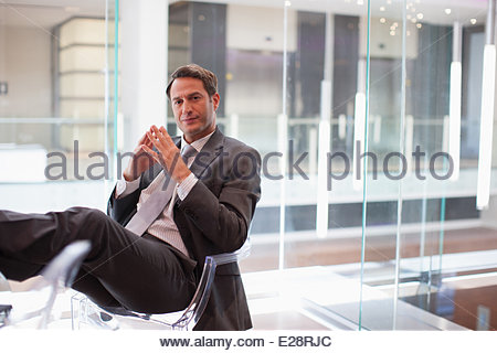 Businessman sitting at desk with feet up - Stock Photo