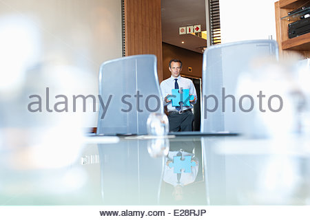 Businessman  holding jigsaw puzzle pieces in conference room - Stock Photo