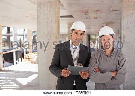 Construction workers standing together on construction site - Stock Photo