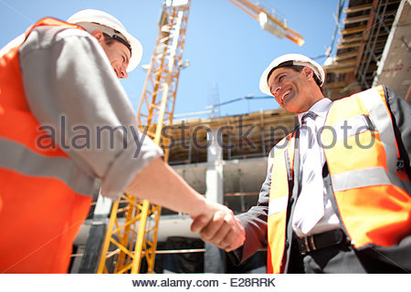 Construction workers shaking hands on construction site - Stock Photo