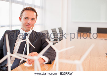 Businessman sitting with model wind turbines in conference room - Stock Photo