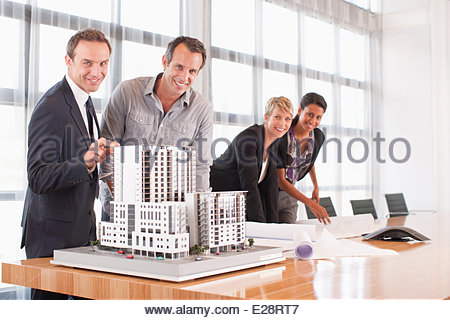 Business people looking at blueprints and model building - Stock Photo