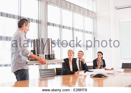 Business people looking at model building - Stock Photo