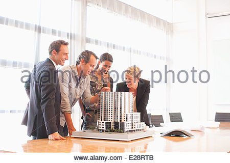 Business people looking at model building in conference room - Stock Photo