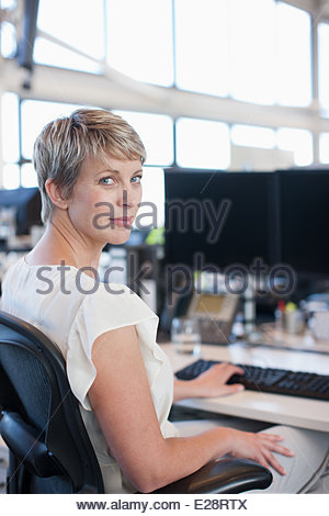 Businesswoman working at desk in office - Stock Photo