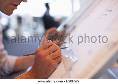 Businessman drawing on drafting table in office - Stock Photo