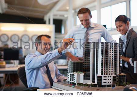 Architects looking at building model in office - Stock Photo