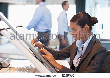 Businesswoman drawing on drafting table in office - Stock Photo