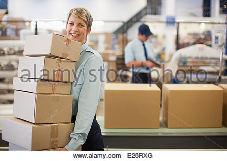 Worker carrying boxes in shipping area - Stock Photo